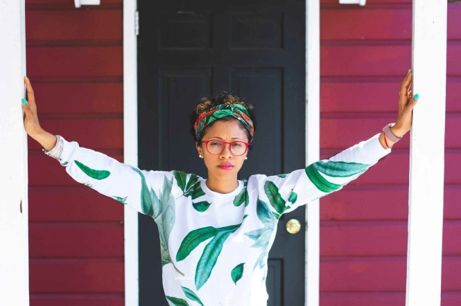 woman wearing green and white sweater near black wooden door